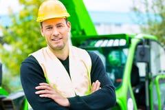 Byggnadsarbetare på plats i hydraulisk lyftande ramp royaltyfri foto