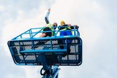 Byggnadsarbetare på plats i hydraulisk lyftande ramp royaltyfria bilder