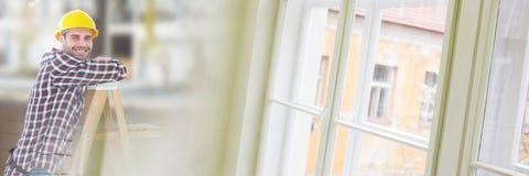 Byggnadsarbetare på stege framme av konstruktionsplatsen med fönsterövergångseffekt Arkivfoton