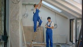 Byggnadsarbetare på stege i hus lager videofilmer