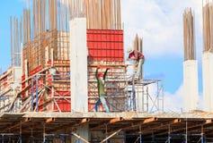 Byggnadsarbetare placerar och byggnad av hus på utomhus- arbetarearbete vilket har himmelbakgrund med kopieringsutrymme att tillf arkivbilder