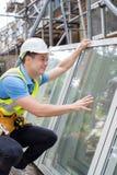 Byggnadsarbetare Preparing To Fit nya Windows royaltyfri bild