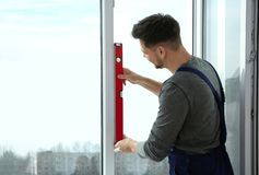 Byggnadsarbetare som använder bubblanivån, medan installera fönstret royaltyfri foto