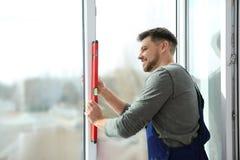 Byggnadsarbetare som använder bubblanivån, medan installera fönstret royaltyfria bilder