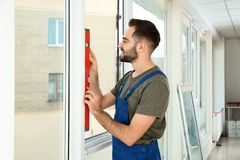 Byggnadsarbetare som använder bubblanivån, medan installera fönstret royaltyfri bild