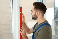Byggnadsarbetare som använder bubblanivån, medan installera fönstret royaltyfri fotografi