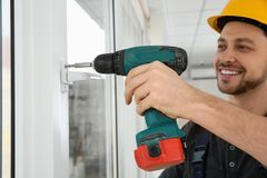 Byggnadsarbetare som använder drillborren, medan installera fönstret royaltyfria foton