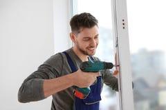 Byggnadsarbetare som använder drillborren, medan installera fönstret arkivfoto