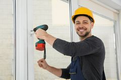 Byggnadsarbetare som använder drillborren, medan installera fönstret arkivfoton