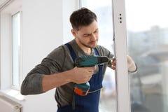 Byggnadsarbetare som använder drillborren, medan installera fönstret fotografering för bildbyråer