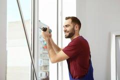 Byggnadsarbetare som använder drillborren, medan installera fönstret royaltyfri bild