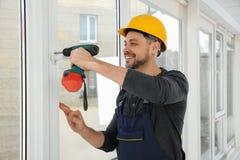 Byggnadsarbetare som använder drillborren, medan installera fönstret arkivbild