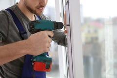 Byggnadsarbetare som använder drillborren, medan installera fönstret inomhus royaltyfria foton