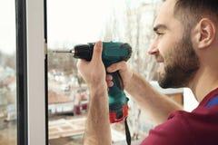 Byggnadsarbetare som använder drillborren, medan installera fönstret inomhus arkivfoton