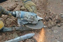 Byggnadsarbetare som använder konstruktionsmolar för att vässa stål på konstruktionsplatsen royaltyfri bild
