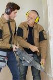 Byggnadsarbetare som använder yrkesmässig drillborrpress royaltyfri fotografi