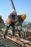 Byggnadsarbetare som använder den konkreta slangen från den konkreta pumpen Arkivfoto