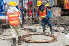 Byggnadsarbetare som arbetar, i att trava för platsbro arkivbilder