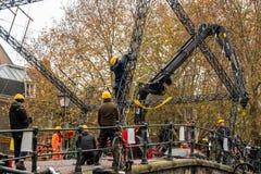 Byggnadsarbetare som bygger och gör reparationer på en stadsstenbro i Amsterdam arkivfoto
