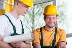 Byggnadsarbetare som diskuterar projekt Arkivfoto