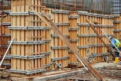 Byggnadsarbetare som fabricerar arbete för förstärkningbetongväggform Arkivbild