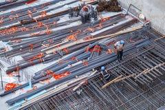 Byggnadsarbetare som fabricerar stålförstärkningstången på konstruktionsplatsen arkivfoton