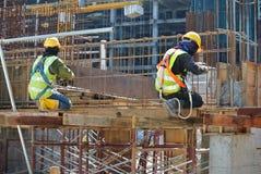 Byggnadsarbetare som fabricerar stången för strålstålförstärkning Royaltyfri Bild