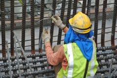 Byggnadsarbetare som fabricerar stålförstärkningstången Arkivbilder