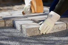 Byggnadsarbetare som fixar en tegelstenväg royaltyfri bild