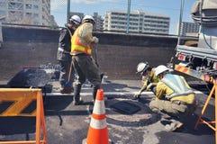 Byggnadsarbetare som fixar v?gen i Tokyo royaltyfri bild