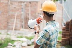 Byggnadsarbetare som ger anvisning till hans anställd arkivfoton