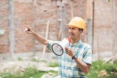 Byggnadsarbetare som ger anvisning till hans anställd royaltyfri bild