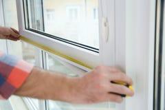 Byggnadsarbetare som inomhus mäter det plast- fönstret, closeup royaltyfri fotografi