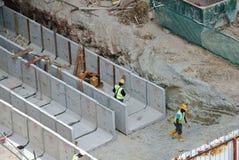 Byggnadsarbetare som installerar avrinningen för färdiggjuten betong Arkivfoton