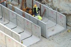 Byggnadsarbetare som installerar avrinningen för färdiggjuten betong Arkivfoto