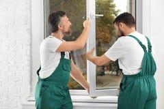 Byggnadsarbetare som installerar det nya fönstret royaltyfria foton