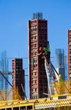 Byggnadsarbetare som installerar formwork på plats royaltyfria foton
