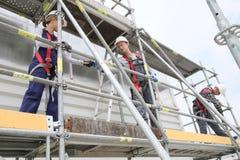 Byggnadsarbetare som installerar materialet till byggnadsställning Arkivfoton