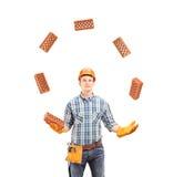 Byggnadsarbetare som jonglerar med tegelstenar Arkivbilder