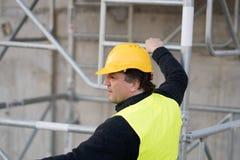 Byggnadsarbetare som klättrar en stege arkivbild