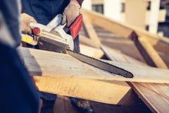 Byggnadsarbetare som klipper timmerträ med chainsawen Män som sågar genom att använda den elektriska chainsawen på takkonstruktio Arkivfoton