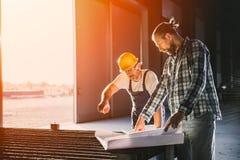 Byggnadsarbetare som kontrollerar kontrollera det blåa trycket Fotografering för Bildbyråer