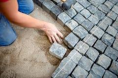 Byggnadsarbetare som lägger kullersten och stenkvarter på trottoar royaltyfria bilder
