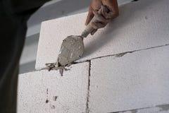 Byggnadsarbetare som renoverar yttre väggar och installerar stenen med mortel royaltyfri foto
