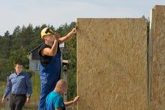 Byggnadsarbetare som reser upp fabrikstillverkade delarna till väggar Royaltyfri Foto