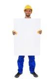 Byggnadsarbetare som rymmer det blanka vita tecknet Arkivfoto