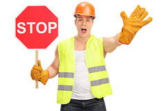 Byggnadsarbetare som rymmer ett stopptecken Arkivfoto