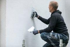 Byggnadsarbetare som sätter dekorativ murbruk på husyttersida Fotografering för Bildbyråer