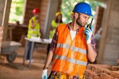Byggnadsarbetare som talar på walkietalkie på platsen Arkivfoto
