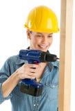 Byggnadsarbetare Using Cordless Drill på träplanka Royaltyfri Foto